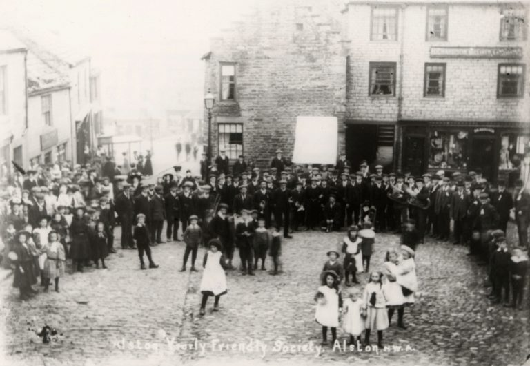 Children And Band In Cobbled Village Square Alston